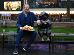 Hugh Bonneville poses with marmalade sandwiches next to the Paddington statue (Victoria Jones/PA)