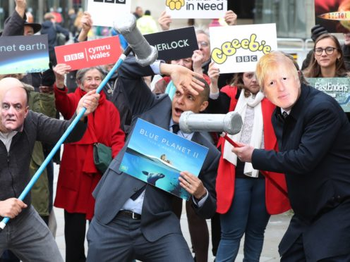 Clive Lewis (centre) adopts a pose of mock terror as activists impersonating Dominic Cummings and Boris Johnson take part in a 'whack a mole' photo call outside BBC New Broadcasting House in London (Jonathan Brady/PA)