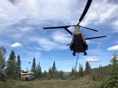 Soldiers use a Chinook helicopter to removed an abandoned bus out of its location in the Alaska back country (Sgt Seth LaCount/Alaska National Guard via AP)