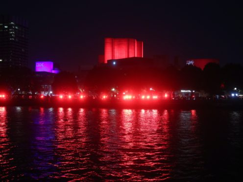 The National Theatre and the South Bank is lit up in red (Yui Mok/PA)