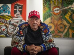 Fashion and portrait photographer David Bailey sits in front of two of his 50 unseen oil paintings (Victoria Jones/PA)