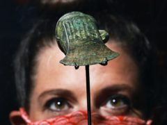 A gallery assistant looks at a socketed axe on display during a preview of the Havering Hoard: A Bronze Age Mystery exhibition at the Museum of London Docklands (Aaron Chown/PA)