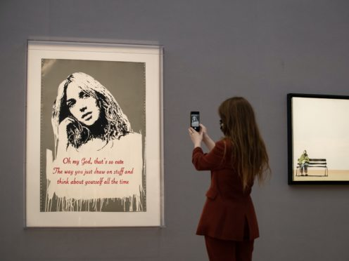 A gallery assistant takes a picture next to Oh My God 2006 by Banksy (Aaron Chown/PA)