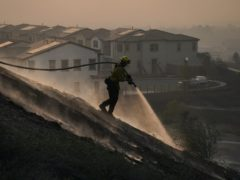 A firefighter puts out hotspots while battling the Silverado Fire (AP)