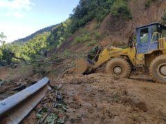 A bulldozer clears a road damaged by a landslide (Bui Van Lanh/VNA via AP)