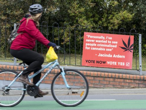 A Christchurch cyclist rides past a sign in support of making marijuana legal (Mark Baker/AP)
