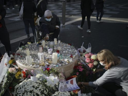 people set flowers, messages and candles in front of the Notre Dame church, in Nice, France, Friday, Oct. 30, 2020. A new suspect is in custody in the investigation into a gruesome attack by a Tunisian man who killed three people in a French church. France heightened its security alert amid religious and geopolitical tensions around cartoons mocking the Muslim prophet. (AP Photo/Daniel Cole)