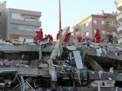 Rescue workers try to save residents trapped in debris of a collapsed building, in Izmir, Turke (Ismail Gokmen/AP)