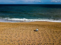 Artist Martin Barraud works on an installation of 749 pairs of bootprints at Slapton Sands in Devon where 749 American soldiers were killed while rehearsing for the D-Day invasion of Normandy (There But Not There/PA)