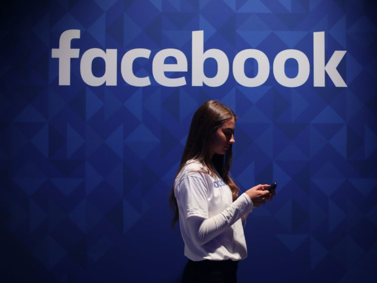A woman using her phone under a Facebook logo (Niall Carson/PA)