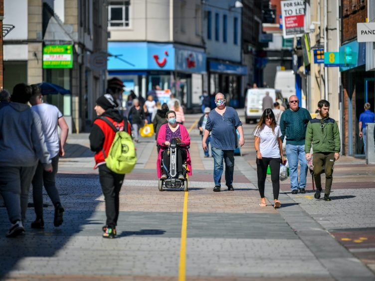 People wear masks on the high street in Merthyr Tydfil (Ben Birchall/PA)
