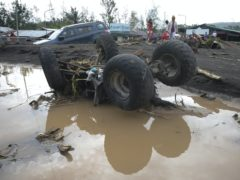 A vehicle is toppled by strong winds and floods from Typhoon Goni in Albay province, Philippines (AP)