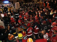 Rescue workers carry 14-year-old Idil Sirin from the wreckage of a collapsed building (IHA via AP)