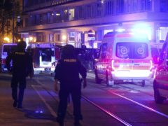 Police officers walk near ambulances at the scene after gunshots were heard in Vienna (Ronald Zak/AP)