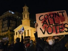 A demonstrator holds up a sign while waiting for election results at Black Lives Matter Plaza, Tuesday, Nov. 3, 2020, in Washington. (John Minchillo/AP)