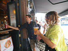 Customers being served takeaway drinks from the Cat & Mutton pub in Broadway Market, London (Yui Mok/PA)