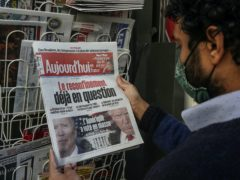 A man reads the headlines about the US election in Paris on Wednesday (Michel Euler/AP)