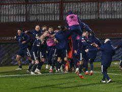 The Scotland players descend on David Marshall (PA)
