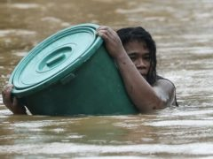 A resident uses a plastic container as a floater while negotiating rising floodwaters in Marikina, Philippines due to Typhoon Vamco (Aaron Favila/AP)