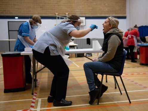 A nurse administers a Covid-19 test at Dimensions Leisure Centre in Stoke-on-Trent (Jacob King/PA)
