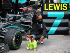 Lewis Hamilton celebrates with his dog Roscoe after winning the Turkish Grand Prix to secure a record-equalling seventh World Drivers' Championship title.