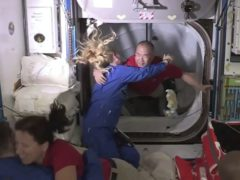 Soichi Noguchi, background right, is greeted by Kate Rubins, as he enters the International Space Station from the vestibule between the SpaceX Dragon capsule and the ISS (NASA TV via AP)