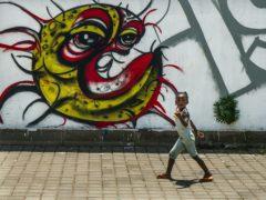 A child walks past a Covid-19 graffiti in Soweto's Orlando West township near Johannesburg (Jerome Delay/AP)