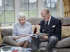 The Queen and Philip reading the card from George, Charlotte and Louis (Chris Jackson/Buckingham Palace/PA)