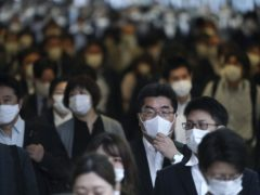A station passageway is crowded with commuters wearing face masks to help curb the spread of the coronavirus during rush hour in Tokyo (Eugene Hoshiko/AP)
