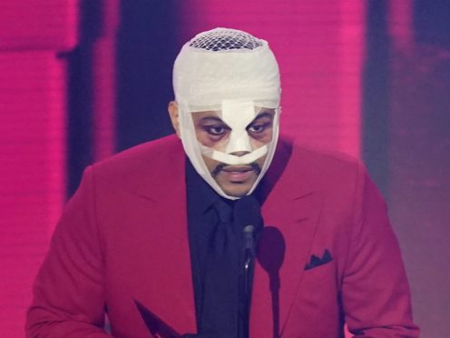 The Weeknd wore bandages wrapped around his face while accepting a price at the American Music Awards (Chris Pizzello/AP)