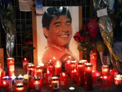 Candles and flowers left for Diego Maradona are seen outside the San Paolo in Naples (Alessandra Tarantino/AP)