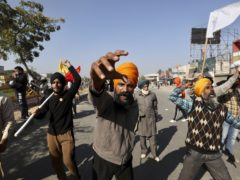 Protesting farmers shout slogans and face security officers at the border between Delhi and Haryana state (Manish Swarup/AP)