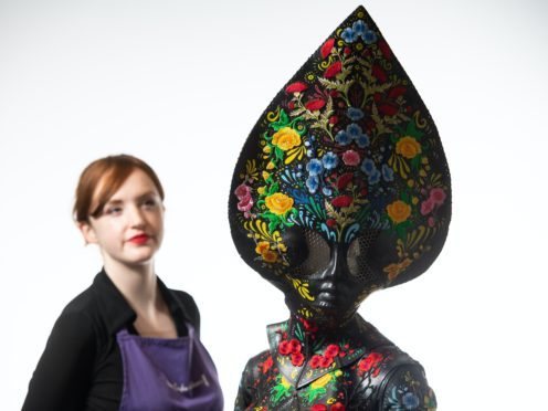 Auctioneer Lucy Bishop views the 'Floral Alien' costume worn by Lady Gaga for her music video '911' (Dominic Lipinski/PA)
