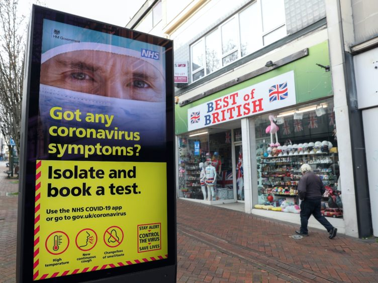 A person walks past a Government coronavirus sign on Commercial Road in Bournemouth, Dorset (Andrew Matthews/PA)