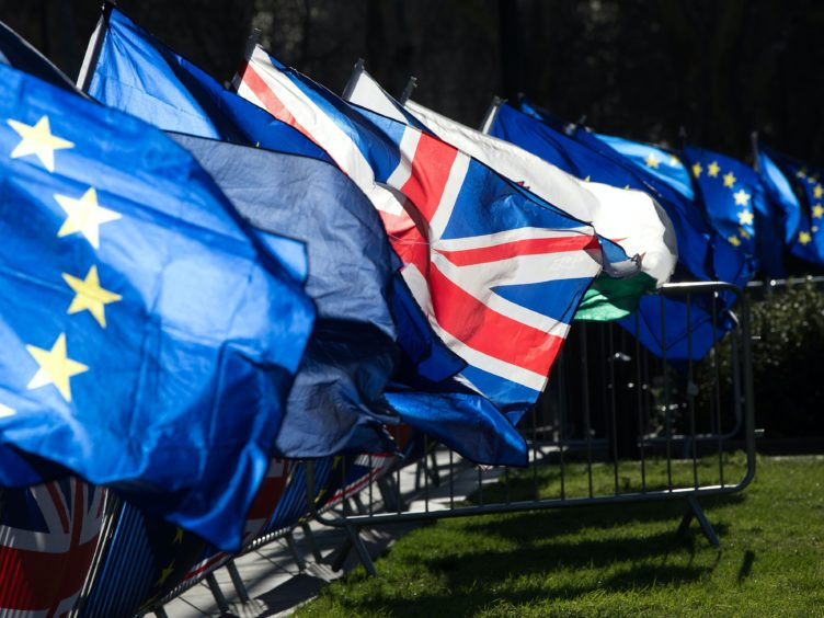 Anti-Brexit campaigners wave Union and European Union flags (Jonathan Brady/PA)