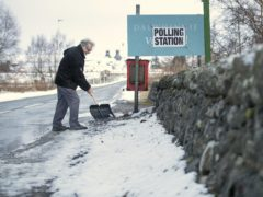 A man clears snow outside a polling station in Dalwhinnie in the Cairngorms, during the 2019 general election (Jane Barlow/PA)