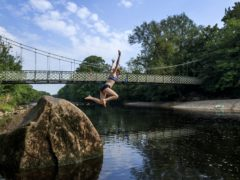 A person jumps from a rock into the River Wharfe near Ilkley in Yorkshire (Danny Lawson/PA)