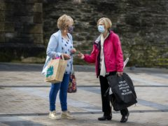 Two woman chat while wearing faces masks (Liam McBurney/PA)
