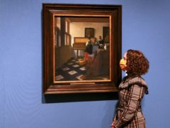 A woman looks at Lady at the Virginals with a Gentleman (The Music Lesson) by Johannes Vermeer (Steve Parsons/PA)