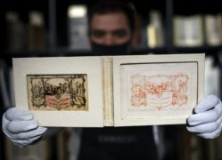 A gallery assistant holds the first printing of the first commercial Christmas greetings card (Victoria Jones/PA)