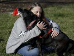 Debra Mejeur hugs her dog Lola after being reunited with her (Youngrae Kim/Chicago Tribune via AP)
