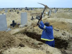 A grave digger prepares graves in Port Elizabeth amid a second wave of coronavirus in South Africa (AP/Theo Jeftha)