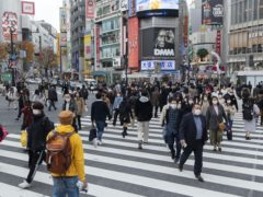 People, wearing face masks walk across an intersection in Tokyo. Coronavirus rates in Japan have been on the rise (Hiro Komae/AP)