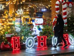 A shopper passes a Christmas light display outside a store in Mayfair, central London (Dominic Lipinski/PA)