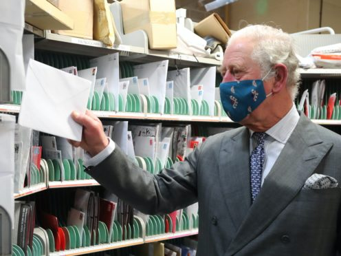 The Prince of Wales helps to sort letters during a visit to Royal Mail's Delivery Office, in Cirencester, to recognise the vital public services that the country's postal workers provide, especially this year and in the run-up to Christmas (Geoff Caddick/PA)