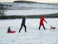 A family takes advantage of the Christmas Day snow with a trip out sledging on the hills near Hexham, Northumberland (Owen Humphreys/PA)