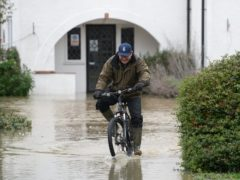 A man cycles through flood water at The Barn Hotel in Bedford (Joe Giddens/PA)