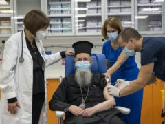 Clergyman Agios Vlasios receives an injection in Athens (Alkis Konstantinidis/Pool via AP)