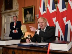 UK chief trade negotiator, David Frost looks on as Prime Minister Boris Johnson signs the EU-UK Trade and Cooperation Agreement at 10 Downing Street (Leon Neal/PA)