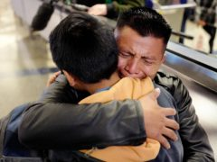 David Xol-Cholom, of Guatemala, hugs his son Byron at Los Angeles International Airport as they reunite after being separated during the Trump administration's wide-scale separation of immigrant families (Ringo HW Chiu/AP)